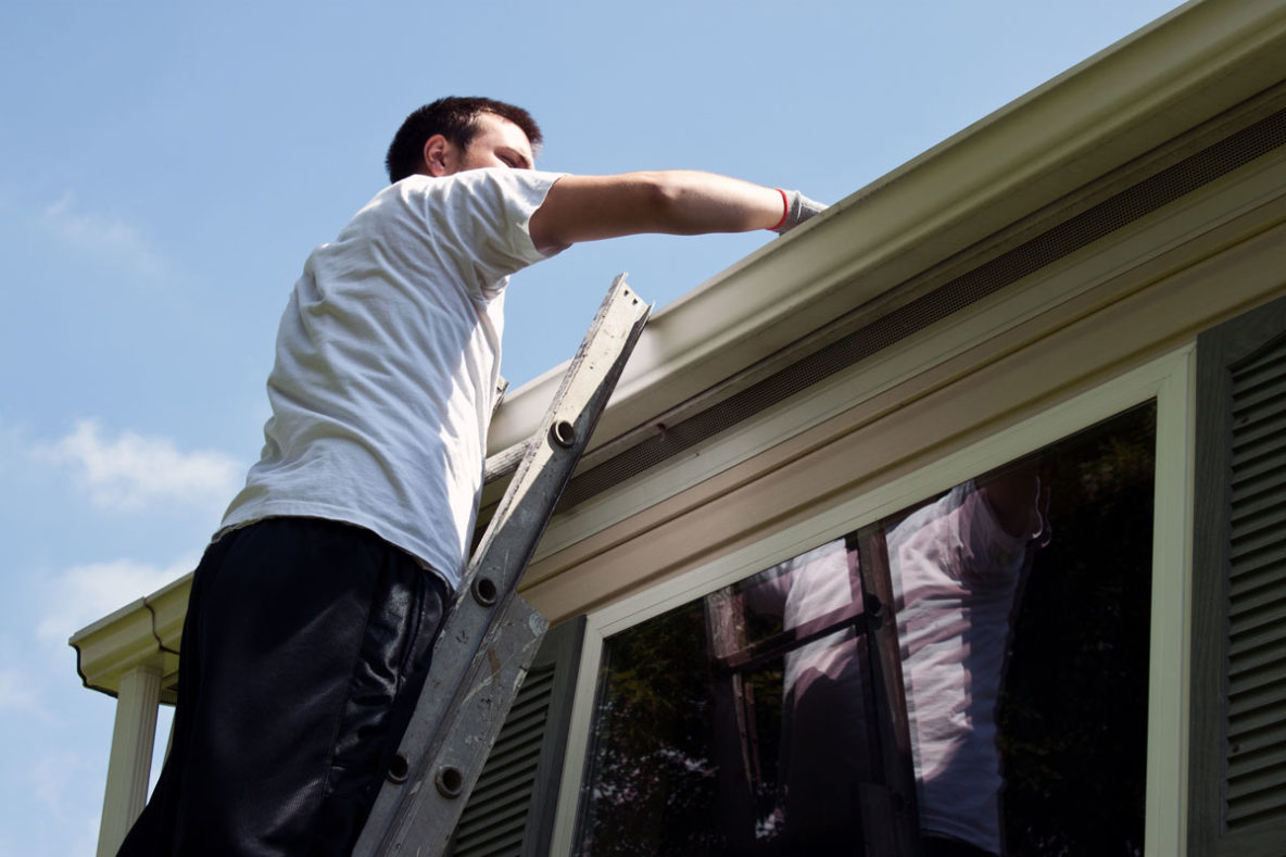 man cleaning roofing gutters